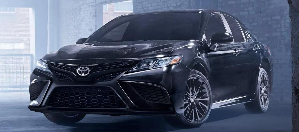Black 2022 Toyota Camry Hybrid in a confined smoky background