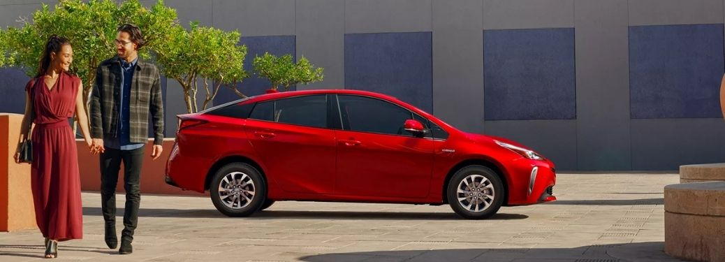 a couple walking beside the parked red 2022 Toyota Prius