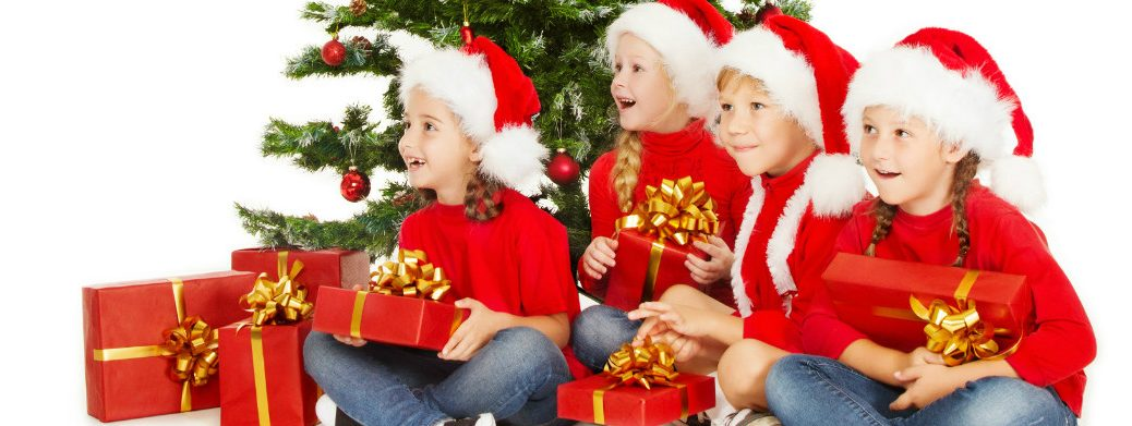 Children in Santa Claus Hats Holding Presents Under the Christmas Tree