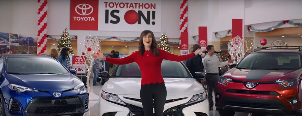 Women Standing in Front of Toyota Models and Toyotathon IS ON Banner