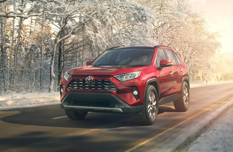 Red 2019 Toyota RAV4 Driving by a Snowy Forest