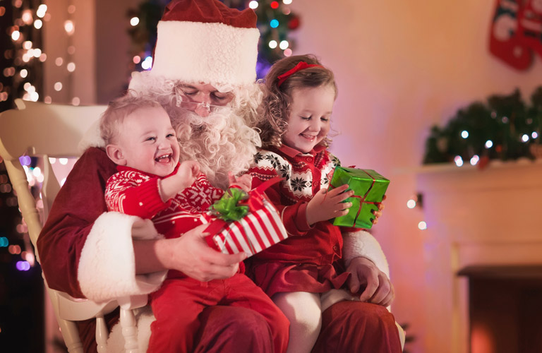 Two kids sitting on a rocking chair with Santa