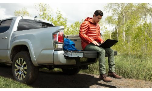 2020 Toyota Tacoma grey tailgate down man on laptop