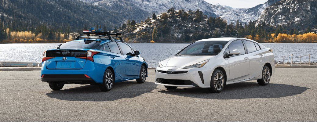 2020 Toyota Prius blue and white paint models parked beside mountain lake