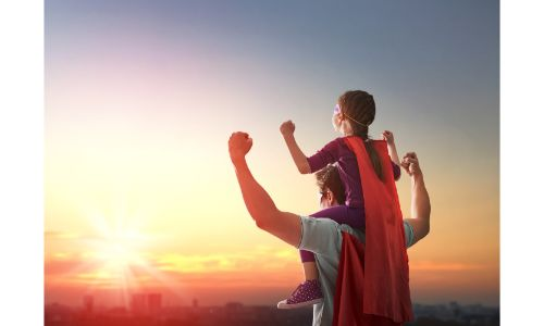 stock photo of dad and son wearing capes flexing in front of sunset