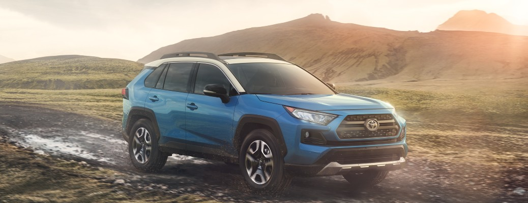 2020 Toyota RAV4 blue and white driving on muddy road with sunburst