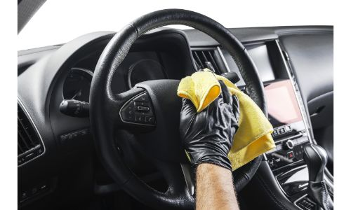stock photo of gloved hand with yellow cloth wiping steering wheel