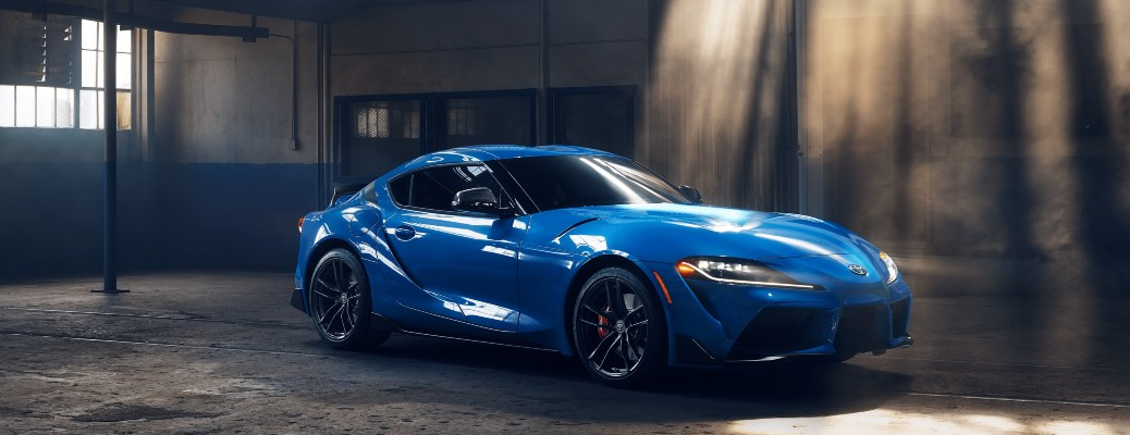 2021 Toyota Supra blue parked in dusty warehouse sunbeams