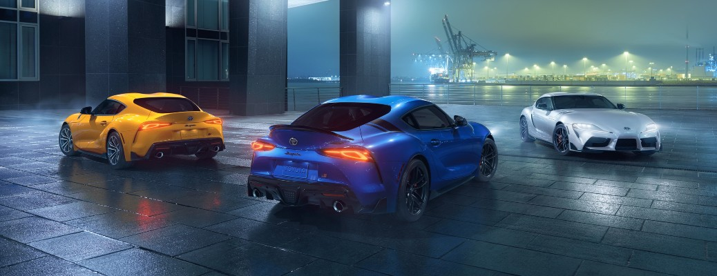 2021 Toyota GR Supra yellow blue and white models parked on misty night at pier