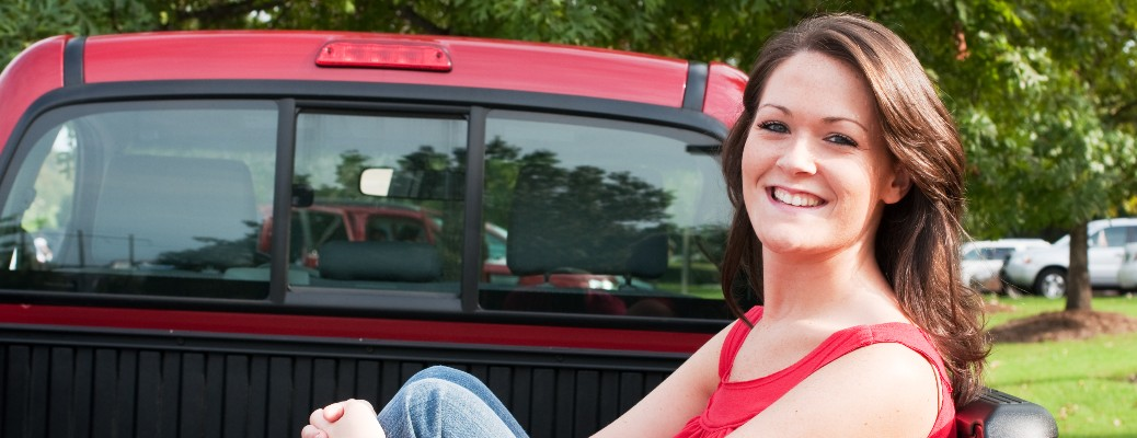 woman sitting in the back of red truck in front of green trees and grass