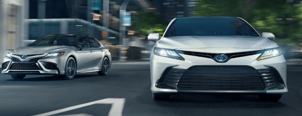 2021 Toyota Camry white and silver models moving on the street
