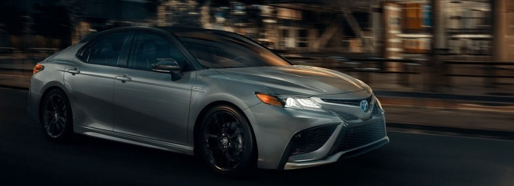 2021 Toyota Camry Hybrid Celestial Silver Metallic moving on the road