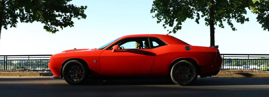 Orange 2019 Dodge Challenger parked near a black fence