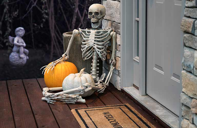 A skeleton sitting next to a door and holding onto two pumpkins