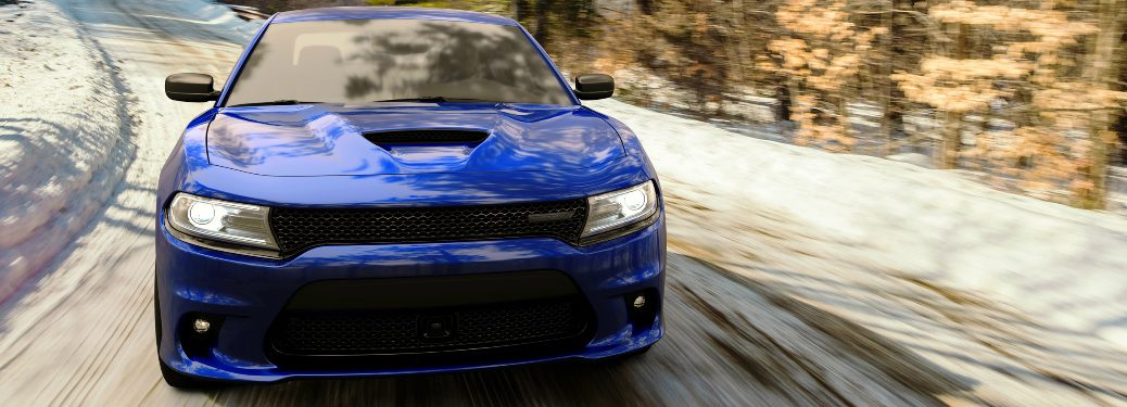 Front view of blue 2020 Dodge Charger GT AWD driving on a snowy road