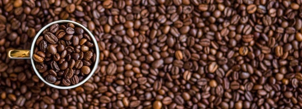 mug filled with coffee beans surrounded by coffee beans