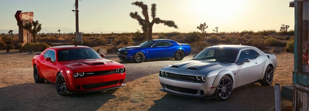 Three 2021 Dodge Challenger muscle-cars in red, blue and silver colorways standing aggressively in the desert at high sun