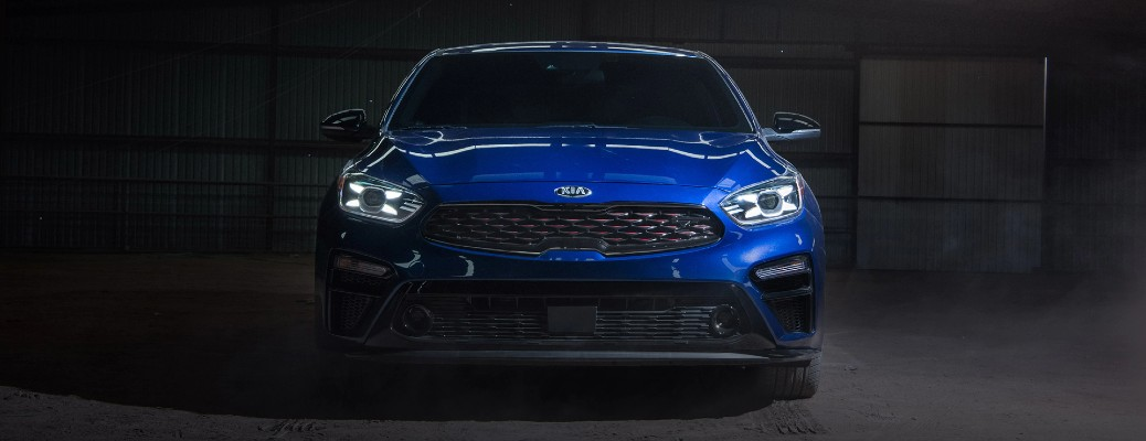 2021 Kia Forte GT exterior front shot with blue paint color parked inside an empty metal garage