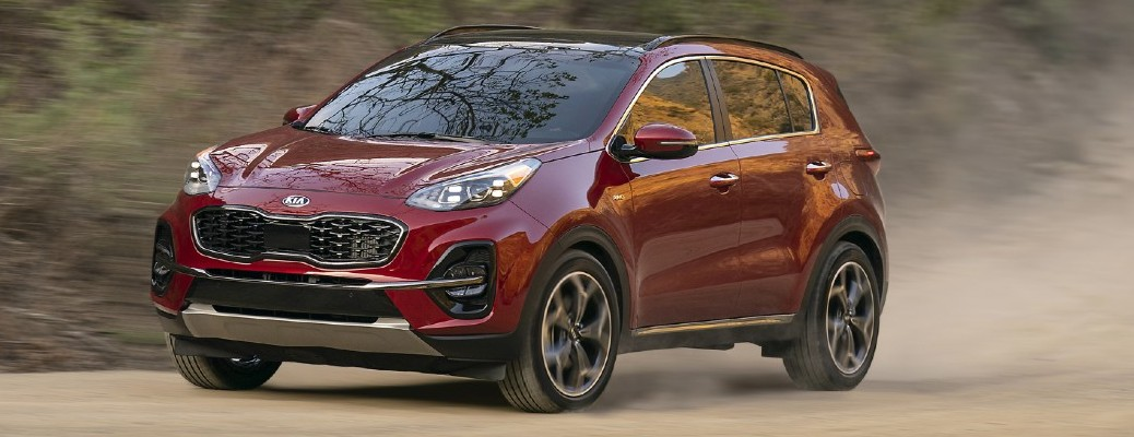 Red 2021 Kia Sportage driving down road with dust flying behind it