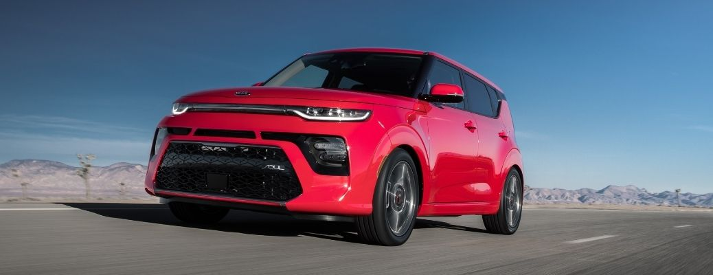 Red 2021 Kia Soul driving on a road.