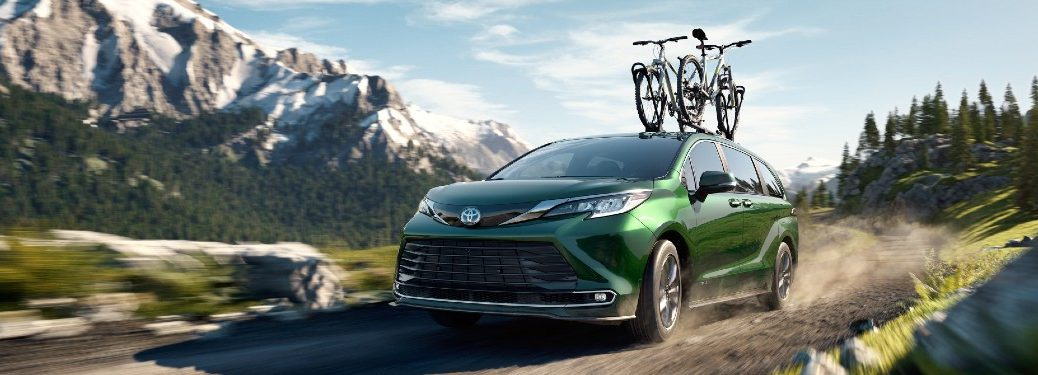 2021 Toyota Sienna green exterior front fascia bikes on roof rack driving on gravel road