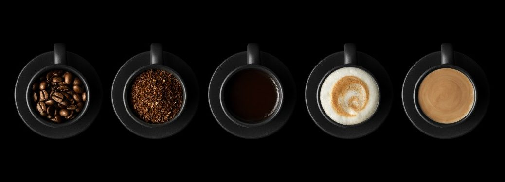 five black coffee cups with beans, grounds, black coffee, latte and cream