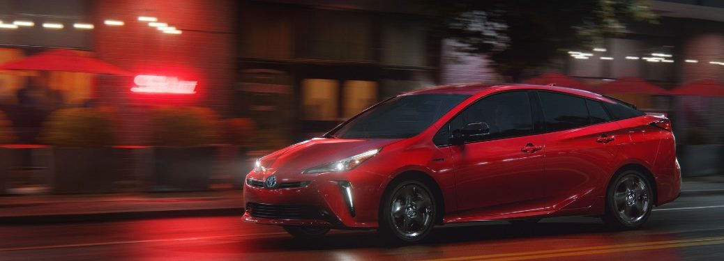 2021 Toyota Prius red exterior drive side driving in city at night