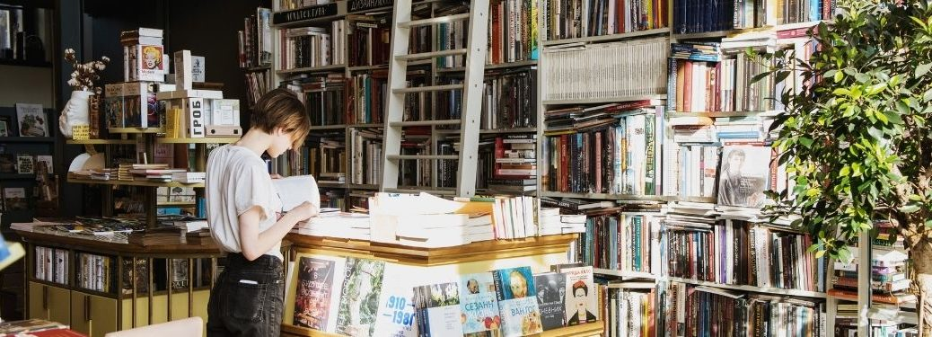 young woman shopping inside of bookstore