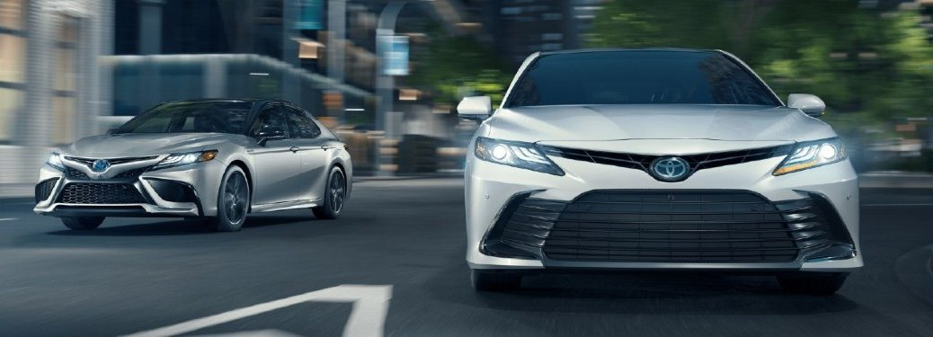 two 2021 Toyota Camry models front fascia driving around curve in city