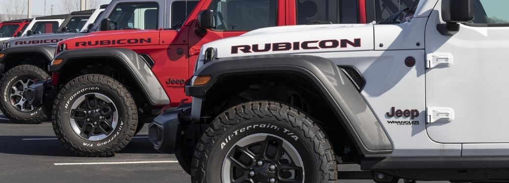 Red and White Jeep Rubicon laying parallel