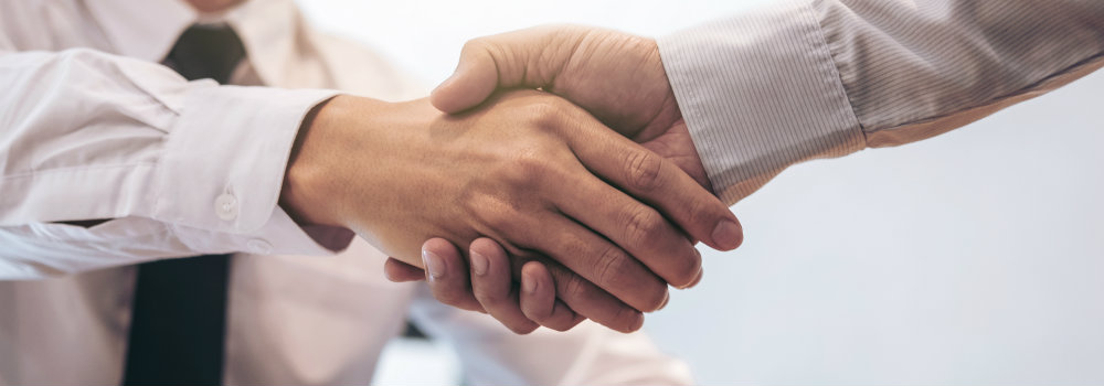 Two men shaking hands inside dealership