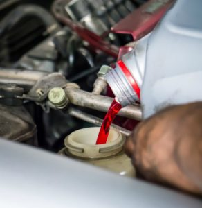 pouring transmission fluid into an engine
