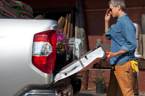 Driver loading 2018 Toyota Tundra truck bed with dirt and flowers