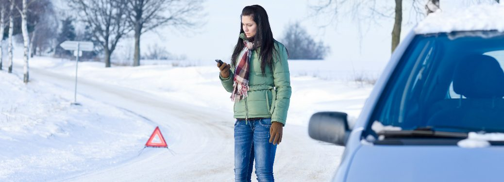 Car driver calling for help on the side of a snow covered road
