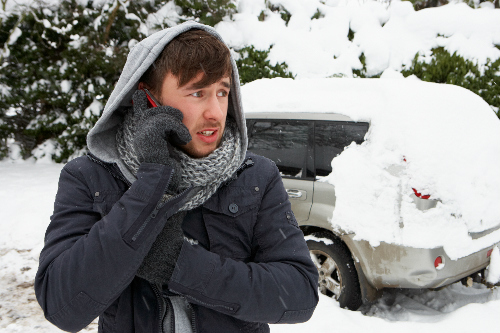 Man calling for help in front of a snow covered van on the side of the road