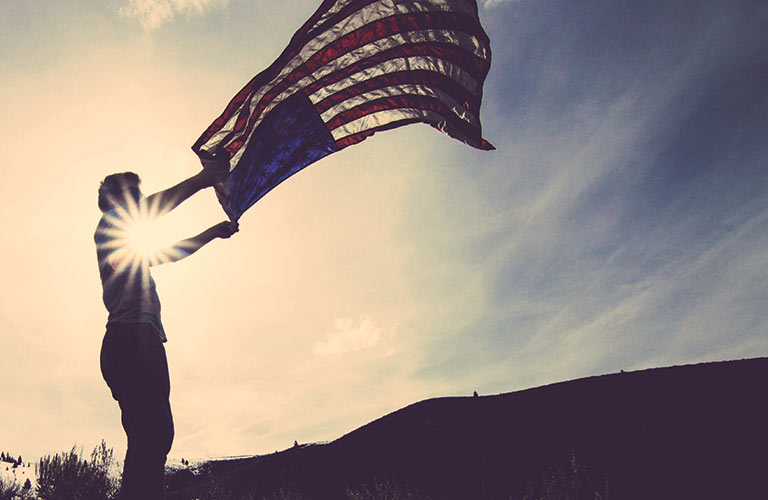Man holding an American flag that is billowing in the wind