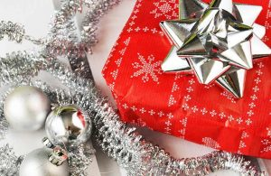 A present in red wrapping paper and a silver bow surrounded by silver tinsel