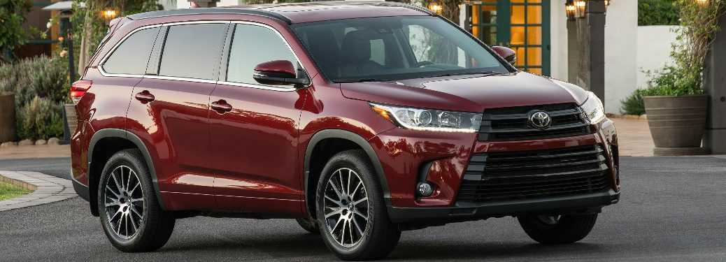 2018 Toyota Highlander in red parked in front of a store