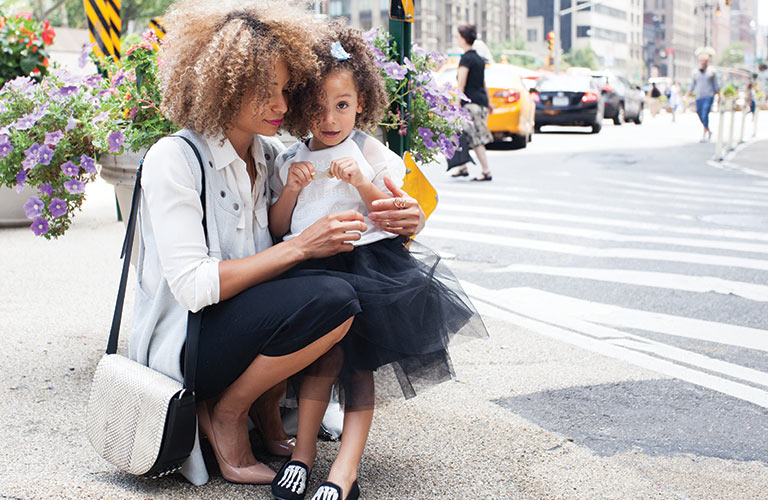 Mother carrying her daughter on a busy city street