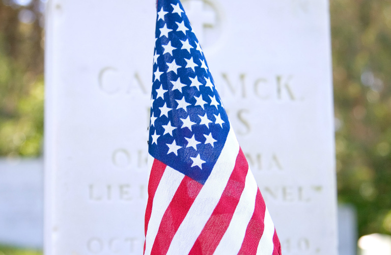 American flag in front of a tombstone