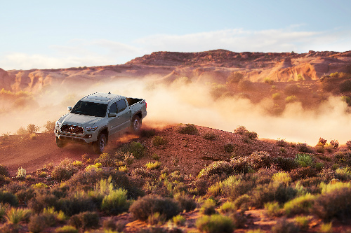 2018 Toyota Tacoma in white driving on dirt hills in the desert