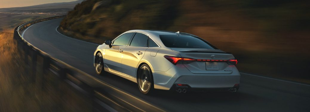 2019 Toyota Avalon driving on a twisty mountain road at sunset
