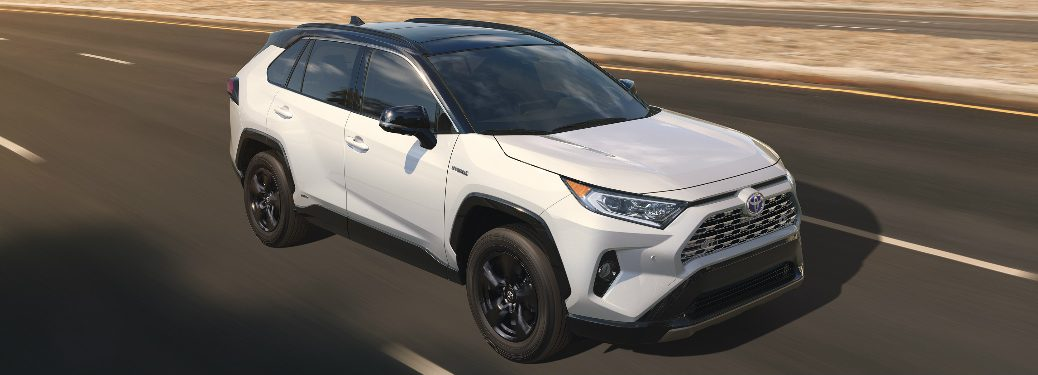 2019 Toyota RAV4 in white driving down an empty road
