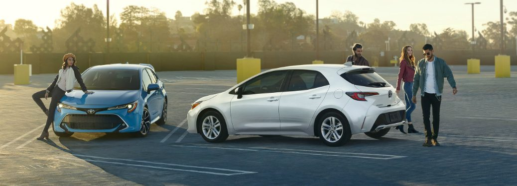People standing next to two 2019 Toyota Corolla Hatchback models parked in an empty lot