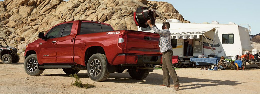Man packing camping supplies into the back of the 2018 Toyota Tundra