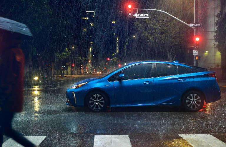 2019 Toyota Prius crossing a rainy intersection at night