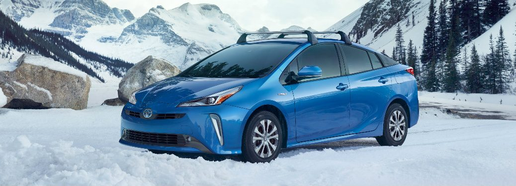 2019 Toyota Prius with roof racks parked in a snowy clearing in the mountains