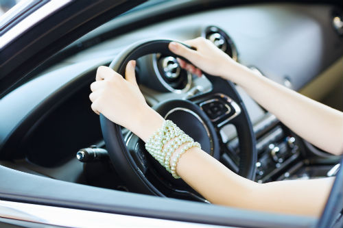 close up of a woman's hands on a steering wheel