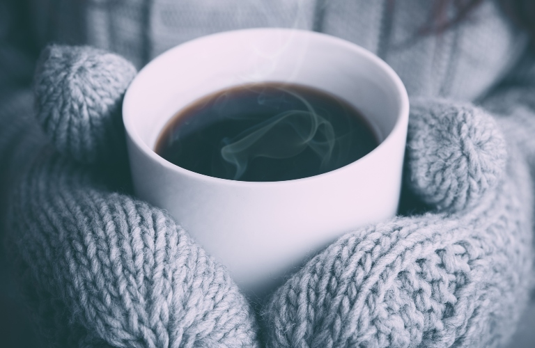 Person holding warm drink with mittens