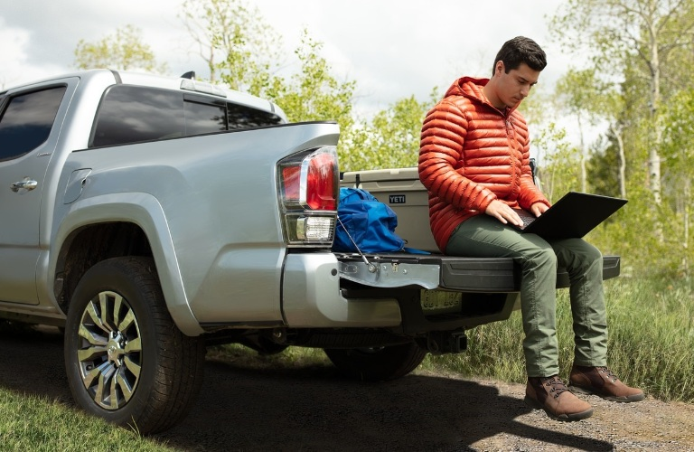 Man sitting on tailgate of 2020 Toyota Tacoma